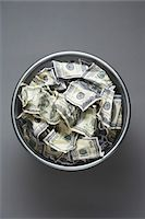 Dollar bills in wastebasket, view from above Stock Photo - Premium Royalty-Freenull, Code: 693-03311177