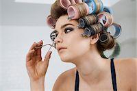 Model in Hair Curlers Using Eyelash Curler Stock