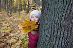Girl holding leaves behind tree in park Stock Photo - Premium Royalty-Free, Artist: Frank Krahmer, Code: 693-03315247