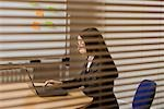 Woman workng in office, view through blinds Stock Photo - Premium Royalty-Free, Artist: Sheltered Images, Code: 693-03317203