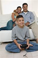 preteen  smile  one  alone - Parents Watching Son Play Video Games in living room, front view Stock Photo - Premium Royalty-Freenull, Code: 694-03318038