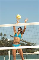 spike - Female beach volleyball player jumping to spike volleyball over net Stock Photo - Premium Royalty-Freenull, Code: 694-03319268
