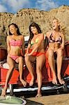 Three young women in bikinis sitting in back of truck Stock Photo - Premium Royalty-Free, Artist: Ty Milford, Code: 694-03319329