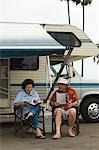 Couple relaxing outside motor home Stock Photo - Premium Royalty-Freenull, Code: 694-03319416