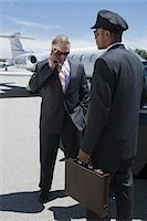 Senior businessman standing outside private jet and talking on phone, Chauffeur holding his suitcase. Stock Photo - Premium Royalty-Freenull, Code: 694-03322043