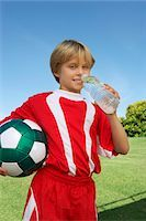 Boy (7-9 years) soccer player holding ball and water bottle, portrait Stock Photo - Premium Royalty-Freenull, Code: 694-03327043