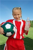 Girl (7-9 years) soccer player holding ball and water bottle, portrait Stock Photo - Premium Royalty-Freenull, Code: 694-03327044