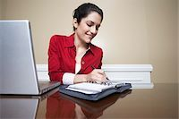 planner - Business woman writing in diary beside laptop in office Stock Photo - Premium Royalty-Freenull, Code: 694-03327617