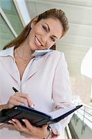 planner - Businesswoman writing in planner while using cell phone outdoors, portrait Stock Photo - Premium Royalty-Freenull, Code: 694-03327969