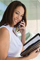 planner - Woman using cell phone holding planner, portrait Stock Photo - Premium Royalty-Freenull, Code: 694-03327977