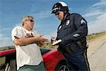 Traffic cop talking with driver of sports car Stock Photo - Premium Royalty-Free, Artist: Beyond Fotomedia, Code: 694-03328503