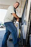 Man Jacking up Vehicle in Service Station Stock Photo - Premium Royalty-Free, Artist: Transtock, Code: 694-03330314
