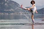 Woman Kicking in Shallow Water,  Fuschlsee, Salzburg, Austria Stock Photo - Premium Rights-Managed, Artist: Bettina Salomon, Code: 700-03333139
