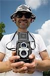 A man holding an analogue camera Stock Photo - Premium Royalty-Free, Artist: Tom Collicott, Code: 653-03333873