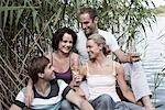 Four friends sitting near a lake Stock Photo - Premium Royalty-Free, Artist: Aurora Photos            , Code: 653-03333894