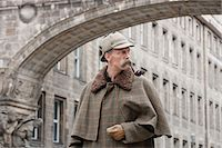 A man dressed up as Sherlock Holmes standing under a building arch looking away Stock Photo - Premium Royalty-Freenull, Code: 653-03334452