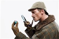 A man dressed up as Sherlock Holmes looking at a tiny globe through a magnifying glass Stock Photo - Premium Royalty-Freenull, Code: 653-03334456