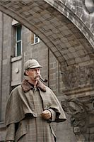 A man dressed up as Sherlock Holmes standing under a building arch looking away Stock Photo - Premium Royalty-Freenull, Code: 653-03334461