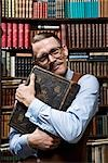 A man holding a book tightly to his chest happily in a bookstore Stock Photo - Premium Royalty-Free, Artist: Matthias Tunger, Code: 653-03334463