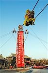 China,Beijing. Beiputuo temple and film studio. Chinese New Year Spring Festival - a lion dance performer climb up a high wire tight rope. Stock Photo - Premium Rights-Managed, Artist: AWL Images, Code: 862-03351541