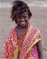 A pretty tousle-haired girl of the nomadic Afar tribe wears bright colours in stark contrast to the drab,windswept surroundings of Lake Abbe. Stock Photo - Premium Rights-Managednull, Code: 862-03352642