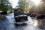 England,Somerset,Exmoor. The ford at Tarr Steps is waded by a four wheel drive - a Landrover Defender 110 with the prehistoric clapper bridge on the right hand side. Stock Photo - Premium Rights-Managed, Artist: AWL Images, Code: 862-03353605