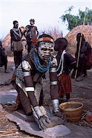 A Nyangatom woman grinds sorghum using two stones. Typical of her tribe,she wears a heavily beaded calfskin skirt,multiple layers of bead necklaces and metal bracelets and amulets. The Nyangatom or Bume are a Nilotic tribe of semi-nomadic pastoralists who live along the banks of the Omo River in south-western Ethiopia. Stock Photo - Premium Rights-Managednull, Code: 862-03354065