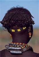 A young Dassanech girl wears a beautiful array of beaded necklaces,some secured at the back by metal rings,and a beaded headband. Her ears are pierced several times,the holes are kept open by small wooden plugs. Much the largest of the tribes in the Omo Valley numbering around 50,000,the Dassanech (also known as the Galeb,Changila or Merille) are Nilotic pastoralists and agriculturalists. Stock Photo - Premium Rights-Managednull, Code: 862-03354079