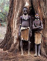 Two young Karo girls stand in front of the massive trunk of a fig tree. A small Omotic tribe related to the Hamar,who live along the banks of the Omo River in southwestern Ethiopia,the Karo are renowned for their elaborate body painting using white chalk,crushed rock and other natural pigments. Stock Photo - Premium Rights-Managednull, Code: 862-03354095