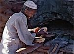 A Nubian baker removes bread from his wood-fired oven.