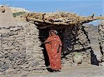 A Nubian woman stands outside her home constructed of stone with a flat earth roof.