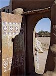 A finely carved painted door graces the arched entrance to a house compound at Qubbat Selim. This village,situated close to the River Nile in Northern Sudan,still retains much of its traditional architecture,plasterwork and decoration..