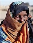 An attractive Nubian woman in bright clothing,the lower part of her face covered by her headscarf.