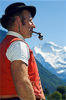 A Swiss man smoking a pipe in traditional alpine costume at the Unspunnen Bicentenary Festival,Interlaken,Jungfrau Region,Switzerland Stock Photo - Premium Rights-Managednull, Code: 862-03354682