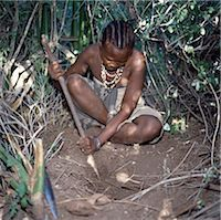A Hadza woman digs for edible tubers with a digging stick.The Hadzabe are a thousand-strong community of hunter-gatherers who have lived in the Lake Eyasi basin for centuries. They are one of only four or five societies in the world that still earn a living primarily from wild resources. Stock Photo - Premium Rights-Managednull, Code: 862-03355173