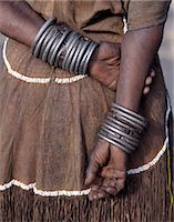 The numerous decorated iron bracelets worn by a Datoga woman. During song and dance,she will rub them together to keep rhythm. Her traditional attire includes a beautifully tanned leather dress embellished with beads. The Datoga (known to their Maasai neighbours as the Mang'ati and to the Iraqw as Babaraig) live in northern Tanzania and are primarily pastoralists. Stock Photo - Premium Rights-Managed, Artist: AWL Images, Code: 862-03355207
