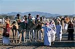 Arab camel handlers lead camels and jockeys into line ready for the start of a race at Al Shaqiyah camel race track. Stock Photo - Premium Rights-Managed, Artist: AWL Images, Code: 862-03360161