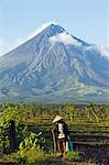 Philippines,Luzon Island,Bicol Province,Mount Mayon (2462m). Near perfect volcano cone with a plume of smoke and farmer with conical hat and walking stick. Stock Photo - Premium Rights-Managed, Artist: AWL Images, Code: 862-03360776