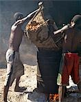 Men tip sugar cane pulp into a drum for boiling with water as the first stage to making rum using a crude open-air still. Stock Photo - Premium Rights-Managed, Artist: AWL Images, Code: 862-03363981