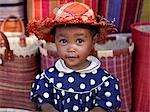 A young girl beside a road-side stall which is offering for sale brightly coloured raffia baskets and hats near Antananarivo,capital of Madagascar.
