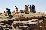 Mali,Dogon Country,Koundu. The women of the Dogon village of Koundu pound their millet communally on a large flat rock near their village. Stock Photo - Premium Rights-Managed, Artist: AWL Images, Code: 862-03364194