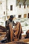 A man working in the tanneries in Old Fez,Morocco. In the white pits,animal hides are soaked for a week in lime and bird droppings to bleach the skin and remove the hair. The skins are then moved to the brown pits where they are coloured using natural dyes. Stock Photo - Premium Rights-Managed, Artist: AWL Images, Code: 862-03364624
