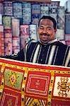 A carpet salesman displays his wares in the souq of Marrakesh