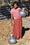 Myanmar,Burma,Mrauk U. A Rakhine girl with aluminium water containers at Mrauk U. These containers are imported from India or Bangladesh. Stock Photo - Premium Rights-Managed, Artist: AWL Images, Code: 862-03365301