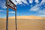 Namibia,Skeleton Coast,Walvis Bay. The sign to the popular tourist dune of Dune 7 located near to Walvis Bay and Swakopmund. Dune 7 is a large sand dune in the Namib Desert,one of the largest in the world and the highest in the coastal belt popular with sandboarders.