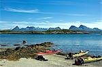 Norway,Nordland,Helgeland. Sea kayaking down the coast of Norway in the summer - a group of kayaks pulled up on the beach with a range of mountains in the background Stock Photo - Premium Rights-Managed, Artist: AWL Images, Code: 862-03365667