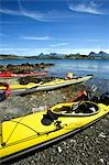 Norway,Nordland,Helgeland. Sea kayaking down the coast of Norway in the summer - a group of kayaks pulled up on the beach with a range of mountains in the background Stock Photo - Premium Rights-Managed, Artist: AWL Images, Code: 862-03365669