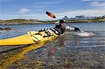 Norway,Nordland,Helgeland. Sea kayaking in coastal Norway during the summer,a guide demonstrated varoius kayaking strokes and techniques in a brightly coloured canoe. Stock Photo - Premium Rights-Managed, Artist: AWL Images, Code: 862-03365671