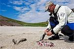 Norway,Nordland,Helgeland. A sea kayak guide prepares a healthy lunch of freshly caught fish on the beach. Stock Photo - Premium Rights-Managed, Artist: AWL Images, Code: 862-03365683