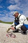 Norway,Nordland,Helgeland. A sea kayak guide prepares a healthy lunch of freshly caught fish on the beach. Stock Photo - Premium Rights-Managed, Artist: AWL Images, Code: 862-03365684
